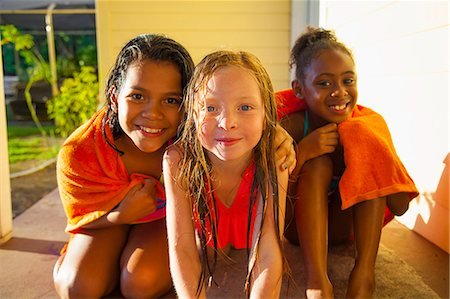 Portrait of three girls wrapped in towel on porch Stock Photo - Premium Royalty-Free, Code: 614-07768094