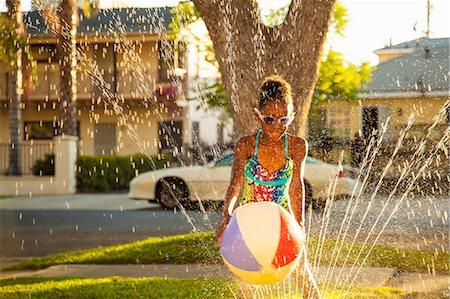Girl with beachball in garden sprinkler Stock Photo - Premium Royalty-Free, Code: 614-07768091