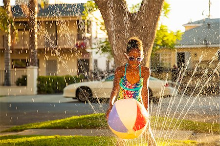 Girl with beachball in garden sprinkler Stock Photo - Premium Royalty-Free, Code: 614-07768091