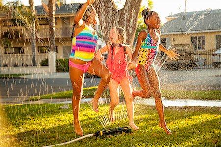 Three girls running and jumping in garden sprinkler Stock Photo - Premium Royalty-Free, Code: 614-07768093