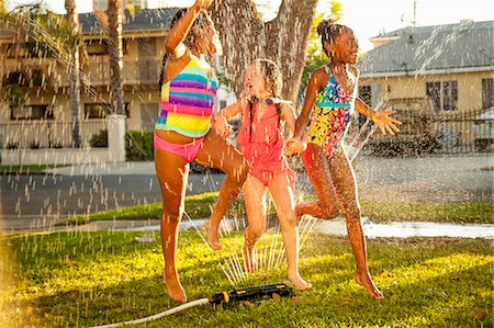 Three girls running and jumping in garden sprinkler Stock Photo - Premium Royalty-Free, Code: 614-07768093