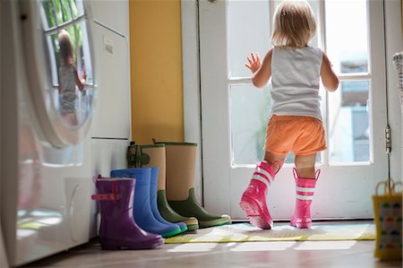 Female toddler wearing rubber boots looking out of back door window Stock Photo - Premium Royalty-Free, Code: 614-07768105
