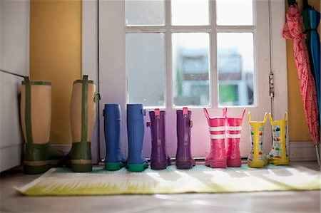 Tidy row of rubber boots at back door Stock Photo - Premium Royalty-Free, Code: 614-07768106