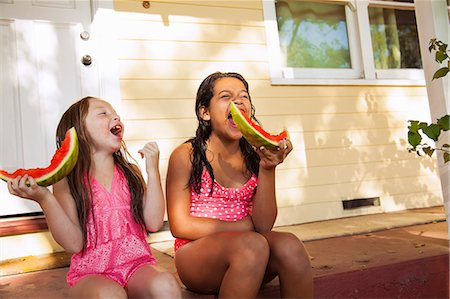 Two laughing girls sitting on house porch with slices of watermelon Stock Photo - Premium Royalty-Free, Code: 614-07768115