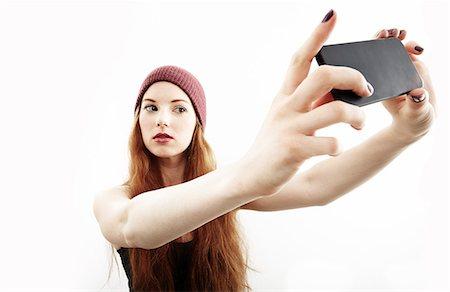 portrait - Studio portrait of young woman making selfie on smartphone Stock Photo - Premium Royalty-Free, Code: 614-07768180