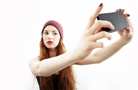 portrait - Studio portrait of young woman making selfie on smartphone Stock Photo - Premium Royalty-Free, Code: 614-07768180