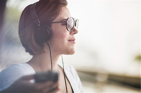 dark glasses - Mid adult woman listening to music on headphones Stock Photo - Premium Royalty-Free, Code: 614-07768229