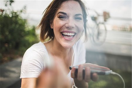 portrait - Portrait of laughing mid adult woman holding up earphone Stock Photo - Premium Royalty-Free, Code: 614-07768236