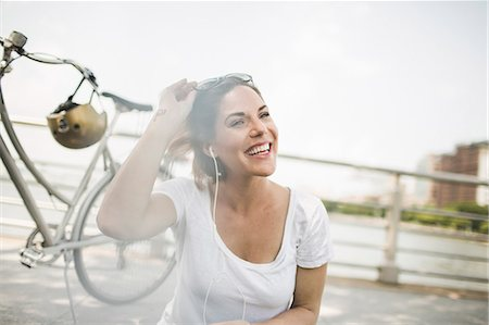 Portrait of smiling mid adult woman cyclist listening to earphones Stock Photo - Premium Royalty-Free, Code: 614-07768237