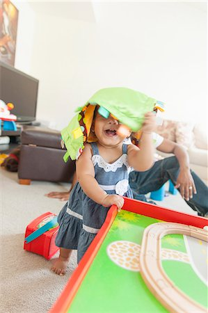 Baby girl playing, father in background Stock Photo - Premium Royalty-Free, Code: 614-07768263