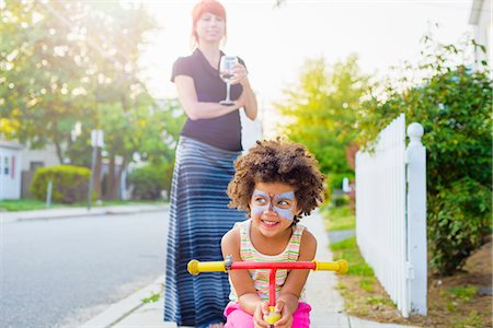Girl with painted face crouching on scooter on suburban street Stock Photo - Premium Royalty-Free, Code: 614-07805730