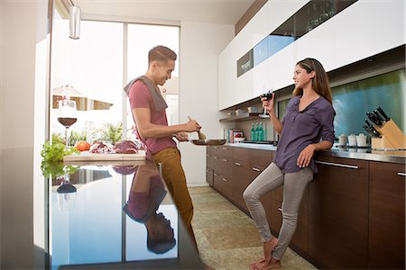 Couple chatting and drinking wine whilst cooking in kitchen Stock Photo - Premium Royalty-Free, Code: 614-07805764