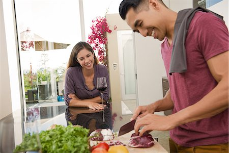 Couple chatting and chopping vegetables in kitchen Stock Photo - Premium Royalty-Free, Code: 614-07805765