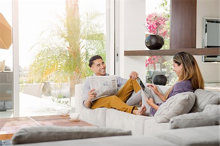 Couple reading newspaper and looking at digital tablet on sitting room sofa Stock Photo - Premium Royalty-Free, Code: 614-07805770