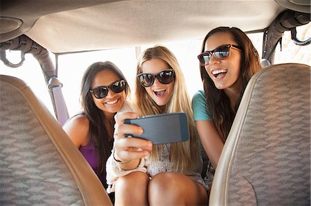 Three young women taking selfie on smartphone in back seat of car Stock Photo - Premium Royalty-Free, Code: 614-07805797