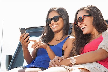 Two young women sitting on jeep hood looking at smartphone Stock Photo - Premium Royalty-Free, Code: 614-07805805