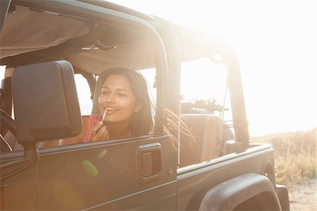 Young woman in jeep at coast applying lip gloss, Malibu, California, USA Stock Photo - Premium Royalty-Free, Code: 614-07805824