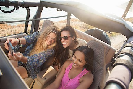 Three young women taking selfie on smartphone in jeep at coast, Malibu, California, USA Stock Photo - Premium Royalty-Free, Code: 614-07805820