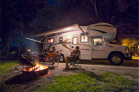 road trip - Mid adult couple and baby daughter sitting in front of campfire at night Stock Photo - Premium Royalty-Free, Code: 614-07805855