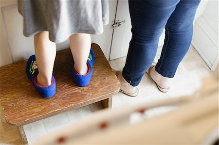 Legs of mid adult mother next to daughter standing on stool in kitchen Stock Photo - Premium Royalty-Free, Code: 614-07805879