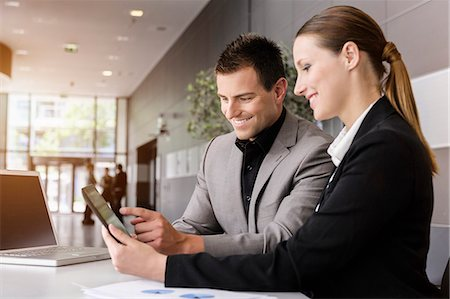 Businesswoman and businessman using digital tablet for discussion Stock Photo - Premium Royalty-Free, Code: 614-07805914