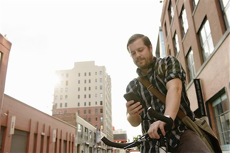 Male cycle messenger checking directions on smartphone Stock Photo - Premium Royalty-Free, Code: 614-07805947