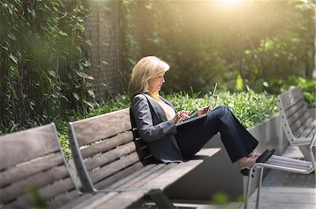 people sitting on bench - Mature businesswoman sitting on bench using laptop Stock Photo - Premium Royalty-Free, Code: 614-07805967