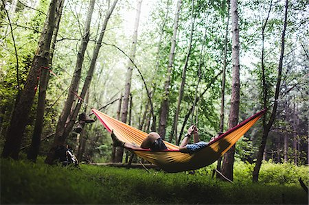 Hiker lying in hammock in forest using digital device Stock Photo - Premium Royalty-Free, Code: 614-07806049