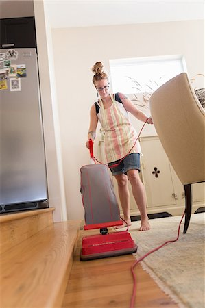 Young woman vacuuming with green cleaning products Stock Photo - Premium Royalty-Free, Code: 614-07806108