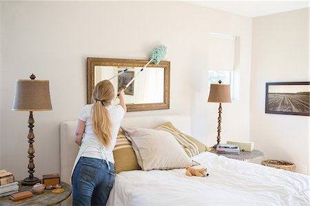 Young woman cleaning bedroom with green cleaning products Stock Photo - Premium Royalty-Free, Code: 614-07806116