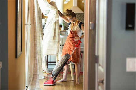 Young woman vacuuming with green cleaning products Stock Photo - Premium Royalty-Free, Code: 614-07806122