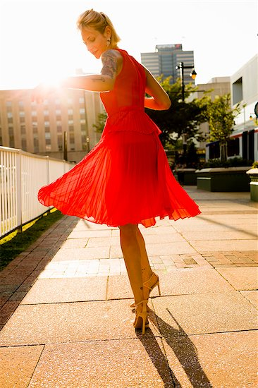 Young woman twirling whilst wearing red dress Stock Photo - Premium Royalty-Free, Image code: 614-07806189