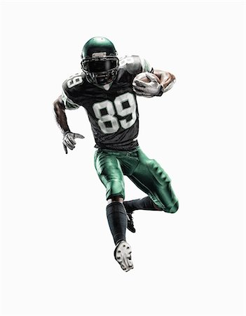 Studio shot of young male football player running with ball Stock Photo - Premium Royalty-Free, Code: 614-07806238