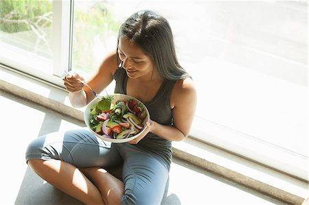 Woman eating salad at home Stock Photo - Premium Royalty-Free, Code: 614-07806265