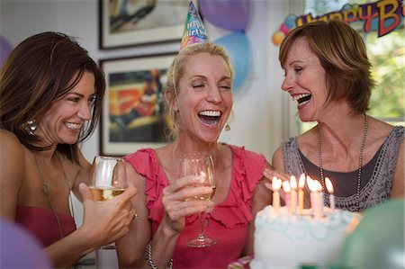 Three mature women at birthday party, laughing Stock Photo - Premium Royalty-Free, Code: 614-07806335