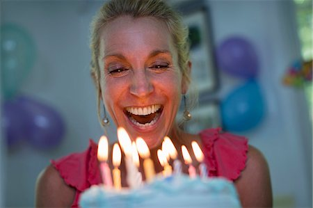 Mature woman holding birthday cake with candles Stock Photo - Premium Royalty-Free, Code: 614-07806336