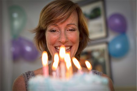 Mature woman holding birthday cake with candles Stock Photo - Premium Royalty-Free, Code: 614-07806337