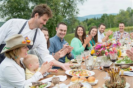 Mid adult man in apron, serving plate of food to family members at table, outdoors Stock Photo - Premium Royalty-Free, Code: 614-07806374
