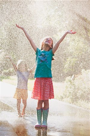 Two girls with arms open standing in water spray on street Stock Photo - Premium Royalty-Free, Code: 614-07806398