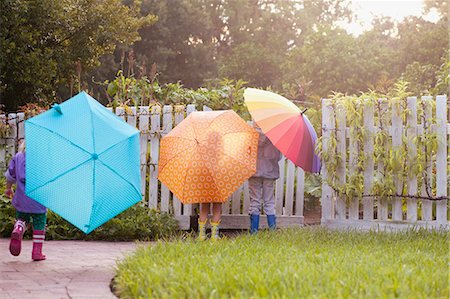 people with umbrellas in the rain - Boy and two sisters playing in garden carrying umbrellas Stock Photo - Premium Royalty-Free, Code: 614-07806393