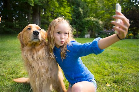 Girl taking selfie with pet dog in garden Stock Photo - Premium Royalty-Free, Code: 614-07806458