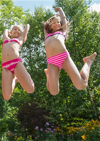 Girls in swimming costume jumping in garden Stock Photo - Premium Royalty-Free, Code: 614-07806469