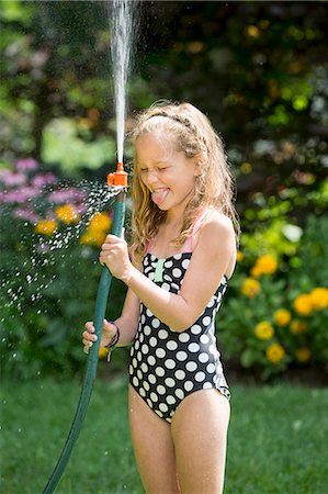 preteen bathing suit - Girl in swimming costume playing with garden hose Stock Photo - Premium Royalty-Free, Code: 614-07806475