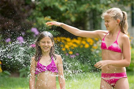 preteen bathing suit - Girls in swimming costume playing with garden sprinkler Stock Photo - Premium Royalty-Free, Code: 614-07806476