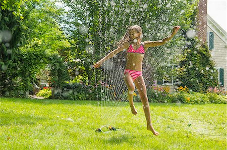Girl in swimming costume jumping over garden sprinkler Stock Photo - Premium Royalty-Free, Code: 614-07806470