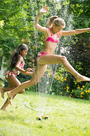 preteen bathing suit - Girls in swimming costume jumping over garden sprinkler Stock Photo - Premium Royalty-Free, Code: 614-07806471
