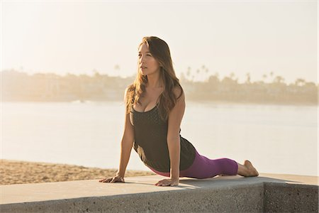 Young woman doing yoga on pier at Pacific beach, San Diego, California, USA Stock Photo - Premium Royalty-Free, Code: 614-07806506