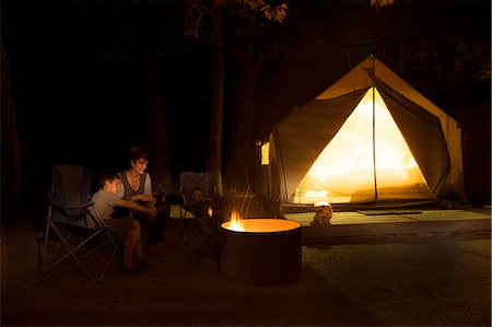 Mature woman and two sons watching campfire at night, County Park, Los Angeles, California, USA Stock Photo - Premium Royalty-Free, Code: 614-07806541