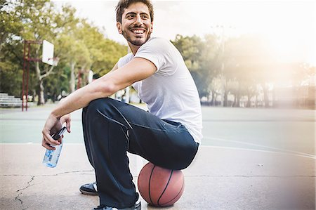 Portrait of young male basketball sitting on ball Stock Photo - Premium Royalty-Free, Code: 614-07911677