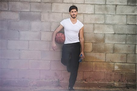 Young male basketball player leaning against wall Stock Photo - Premium Royalty-Free, Code: 614-07911679